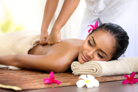 Foto de Balinese massage in spa environment,  deep massage of back - Imagen libre de derechos