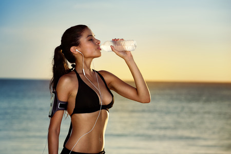 Fitness beautiful woman drinking water and sweating after exercising on summer hot day in beach. Female athlete after workout