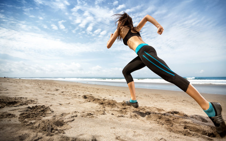 healthy lifestyle sports woman running on seaside