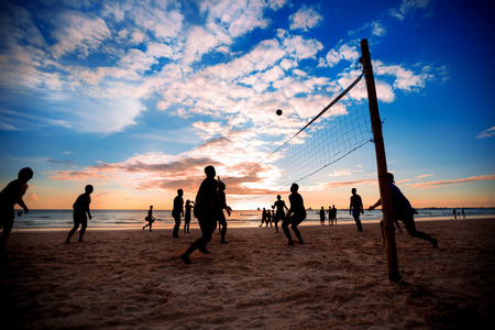 Beach volleyball silhouette at sunset