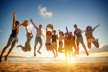 Photo pour Group of young people jumping on beach - image libre de droit