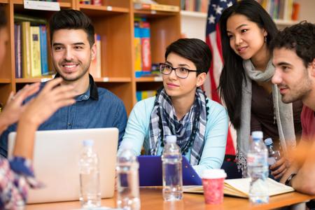 Foto de Group of young students discussing about task - Imagen libre de derechos