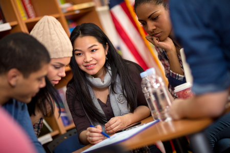 Photo for Multiethnic group of students working on task together - Royalty Free Image