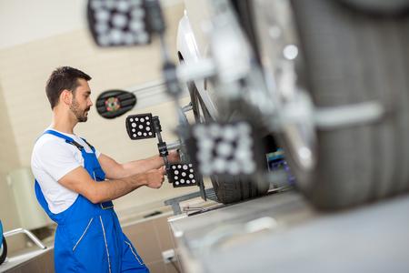 Photo pour car mechanic installing sensor during suspension adjustment - image libre de droit
