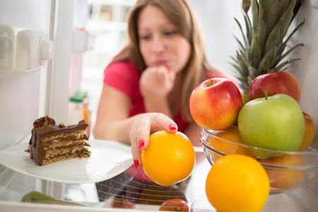 Photo pour Woman hesitating whether to eat piece of chocolate cake or orange - image libre de droit