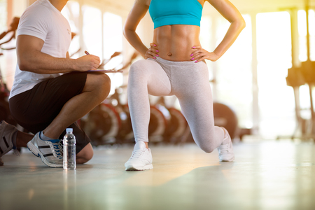 Foto de young sporty woman with trainer exercise in fitness gym - Imagen libre de derechos