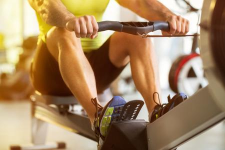 Foto für Fit man training on row machine in gym - Lizenzfreies Bild