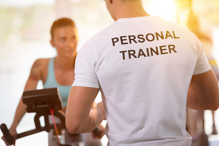 Personal trainer on weights lifting training with  client