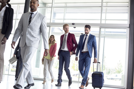 Photo pour Young multiethnic international tourists arrive in airport waiting room - image libre de droit