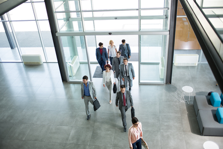 Photo pour Group of professional business people walking on the way in building - image libre de droit