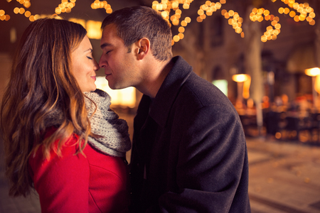 Photo pour Young affectionate couple kissing tenderly on Christmas street - image libre de droit