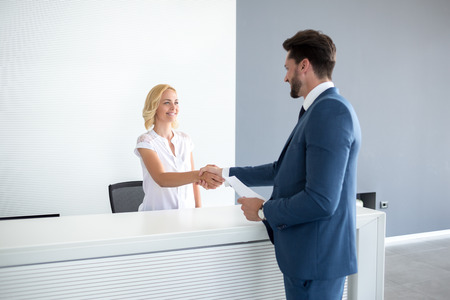 Kind female receptionist wish welcome to guest
