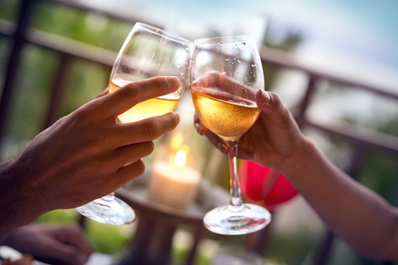 Foto per Hands of man and woman cheering with glasses of white wine - Immagine Royalty Free
