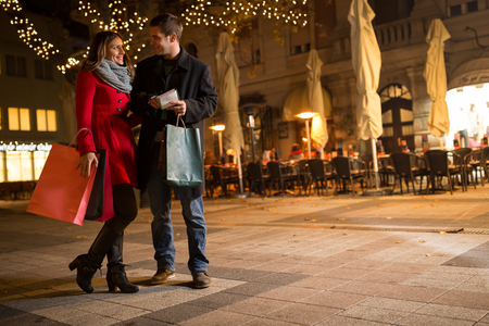 Foto de cheerful young people doing Christmas shopping standing on decorated street - Imagen libre de derechos