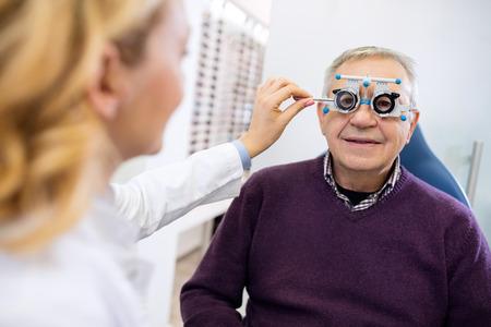 Foto de Male senior in eye clinic examine eyes - Imagen libre de derechos