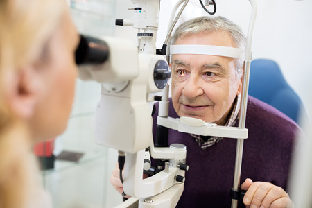 Young female eye specialist determines distance of eyes pupils to patient