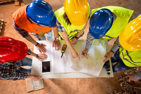 Photo pour Top view of group of architects and engineers checking blue print if construction is going as planned - image libre de droit