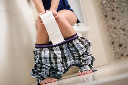 Foto de Woman with stomach problems on toilet - Imagen libre de derechos