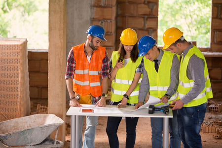 Photo pour Group of young engineers studying blue print at construction site - image libre de droit