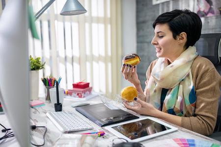 Photo pour satisfied designer eating donuts in office - image libre de droit