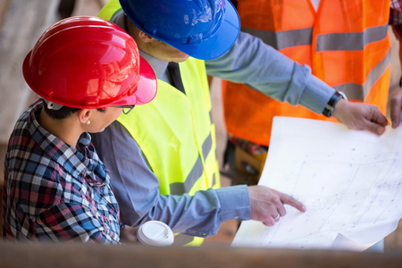 Photo for site manager  looking blueprint with architects - Royalty Free Image