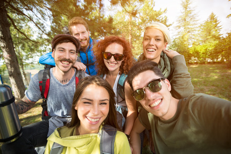 Group photo of cheerful smiling hikers in woods