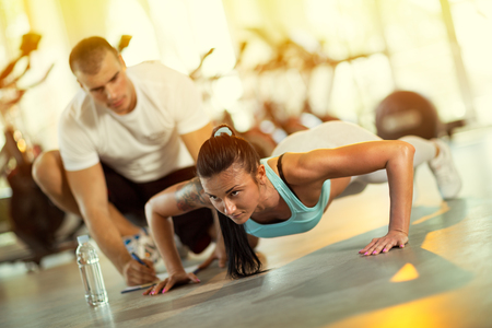 Photo for Young man motivating gym woman  during push ups exercise - Royalty Free Image