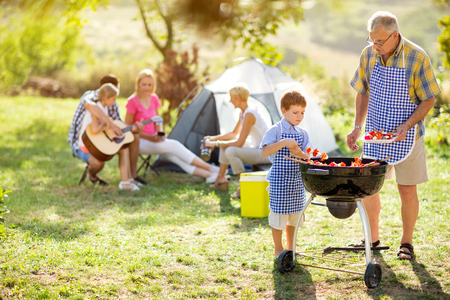 Photo pour happy family on camping making barbecue - image libre de droit