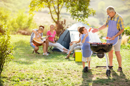 Photo pour grandfather and grandson making barbecue for family - image libre de droit