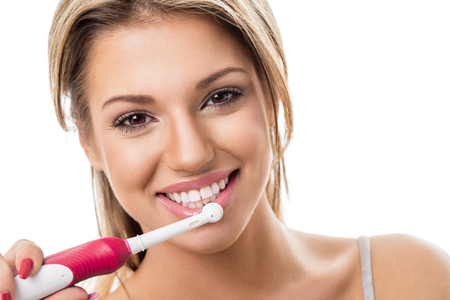 Photo pour Smiling girl with electric toothbrush, brushing teeth - image libre de droit