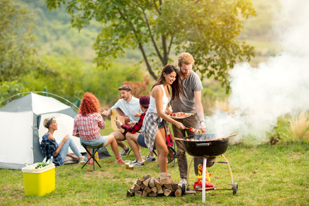 Photo pour Young female and male couple baking barbecue in nature - image libre de droit