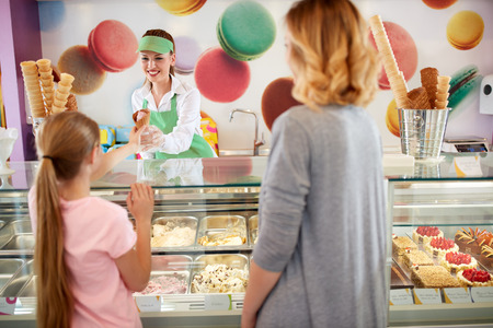 Female seller in bakery gives ice cream to girl