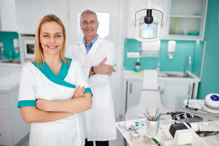 Portrait of pretty female dental assistant with dentist in dental clinic