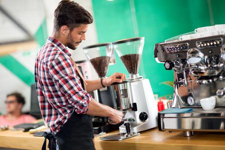 Satisfied barista steaming milk at coffee machine
