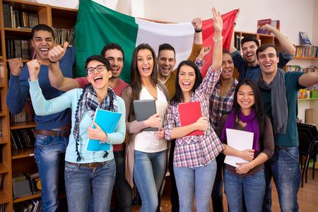 Foto de Smiling students with raised hands presenting Italy with flag - Imagen libre de derechos
