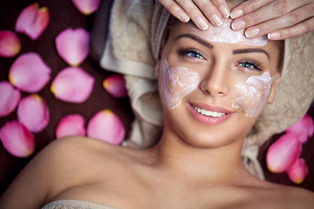 Photo pour Smiling young woman on spa treatment with facial mask - image libre de droit