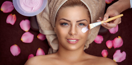 Foto per Cosmetician applying facial mask to the face of young beautiful woman in spa salon - Immagine Royalty Free