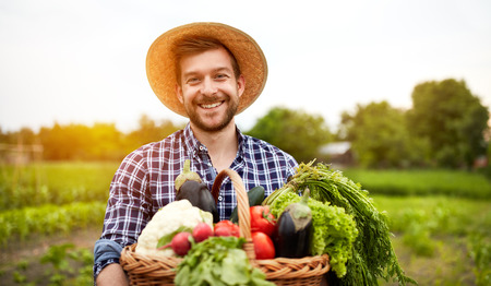 Photo pour Cheerful farmer with organic vegetables in garden - image libre de droit