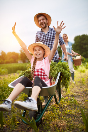 Foto de Delighted girl having fun with male farmer in vegetables garden - Imagen libre de derechos