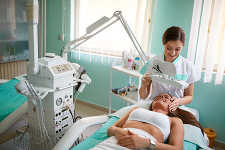 Photo pour Cheerful young girl is getting facial treatment by beautician at spa clinic - image libre de droit