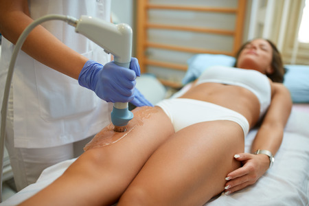 Photo for attractive woman in beauty salon on localized anti fat treatment therapy on the thigh - Royalty Free Image