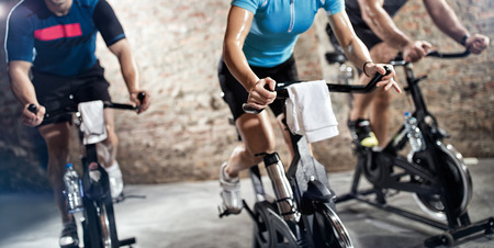 sports clothing people riding exercise bikes, cardio fitness class