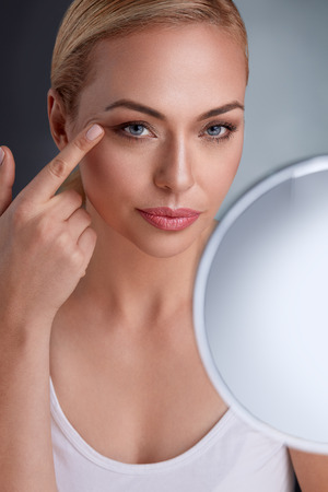 Photo for Beautiful woman with mirror looking her perfect skin - Royalty Free Image