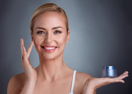 Photo pour Middle aged woman holding cream on palm, natural cosmetic for perfect beauty - image libre de droit