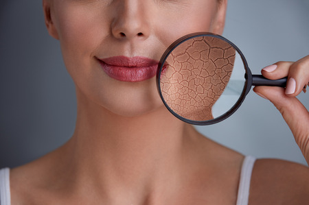 Photo for  face of a beautiful woman with a problem on skin and magnifier - Royalty Free Image