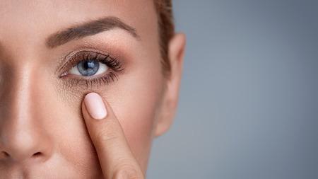 Photo pour woman checking wrinkles around the eyes, close up - image libre de droit