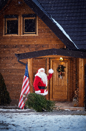 Santa Claus waving when comes in mountain house with Christmas tree