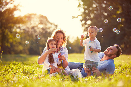 Foto de Family with children blow soap bubbles nature - Imagen libre de derechos