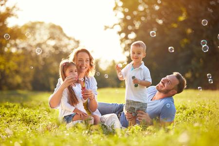 Photo pour Family with children blow soap bubbles outdoor - image libre de droit