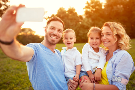 Photo pour Smiling male and female with young son taking photo - image libre de droit